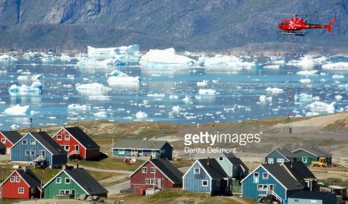 Helicopter flying over town, Narsaq, Greenland